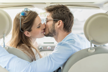 rear view, a lovely couple kissing in a car