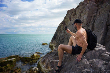 A man sits on the bank of the lake and makes photos of the smartphone