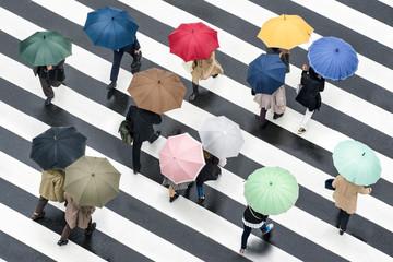 Fotomurales - Fußgänger mit Regenschirm auf einer Kreuzung