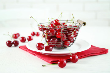 Cherries in basket on table, on light background