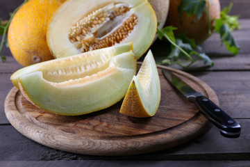 Ripe melons with green leaves on wooden table close up