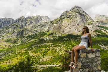 Young woman sitting on a rock and looking at beautiful mountains