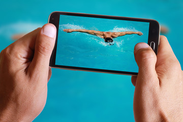 Male hand taking photo of Strong athletic man swimming butterfly style in the pool with cell, mobile phone.