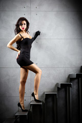 Wall Mural - Sexy brunette woman staying on stairs