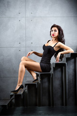 Wall Mural - Sexy brunette woman sitting on stairs