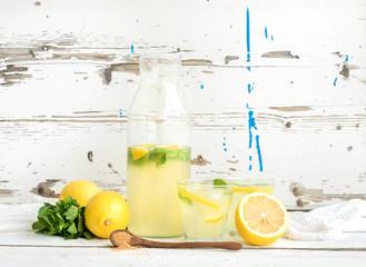 Fresh homemade lemonade with lemons and mint on white wooden
