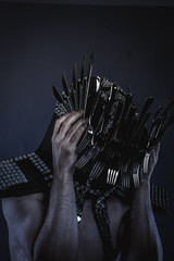 naked man with a crown of spoons and knives in the head, concept