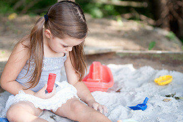 adorable little girl with two pig tails playing in sandbox in