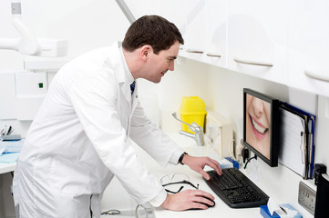 Dentist using computer in dental clinic