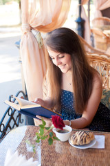 Beautiful woman reading a book in the cafe