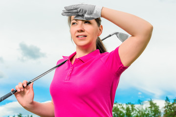 portrait of a girl with a golf club looking out for the flight p