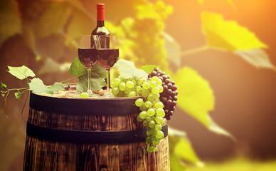 Fototapete - Red wine bottle and wine glass on wodden barrel.
