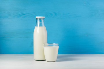 A bottle of rustic milk and glass of milk on a white table on a