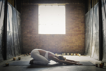 A blonde woman, in a white crop top and leggings, lying on a yoga mat on the floor surrounded by candles, arms outstretched and crouched.