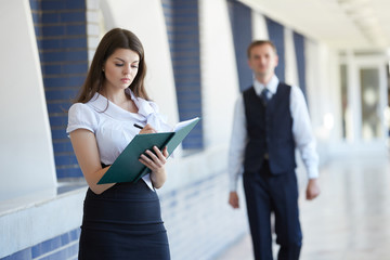 Business woman standing with a notebook, a businessman walking d