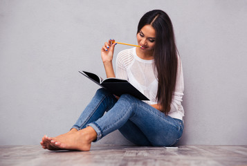 Woman sitting on the floor with notepad and pencil