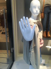 Female mannequin in clothing store with stop hand symbol