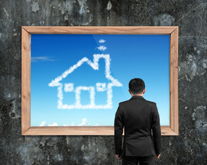 Businessman looking at wooden frame white house shape clouds