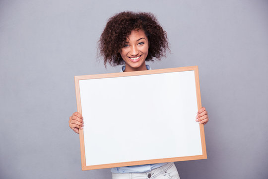 Portrait of a smiling afro american woman holding blank board