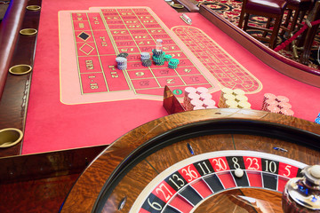 Casino American Roulette gambling table with a wheel and  playing chips on the layout.
