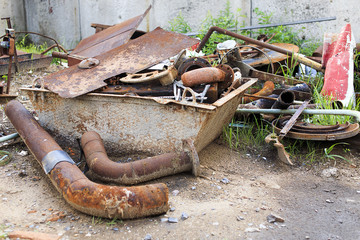 rusty scrap metal. a pile of rusty metal pipes, iron sheets, rods, covers of manholes