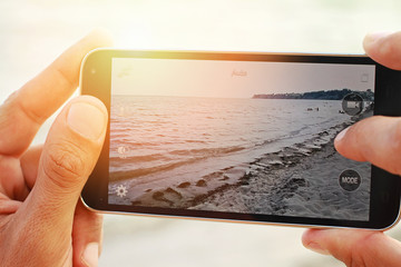 Close up on male hands taking photo of sea coast with mobile cell phone. Summer beach holiday vacation concept. Sunset colors