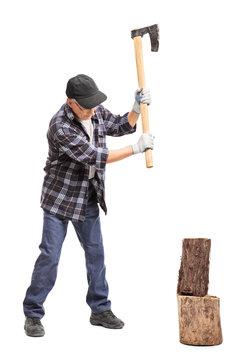 Senior man splitting wood with a hand axe