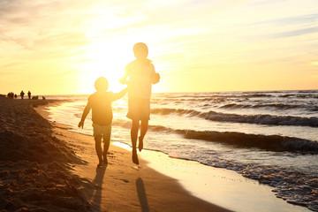 Fototapeta Zabawa przy zachodzie słońca. Dzieci  bawią się na brzegu morza podczas zachodu słońca obraz