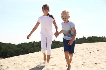 Szczęśliwe dzieci biegają po złotej plaży