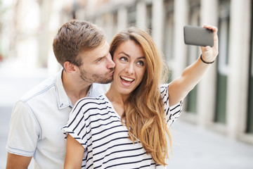 Portrait of a happy couple making selfie photo with smartphone