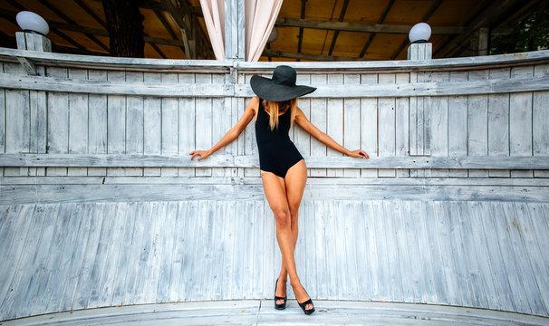 Pretty young girl standing near wooden wall in black swimwear