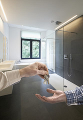 Realtor giving house key to buyer in Luxury Bathroom