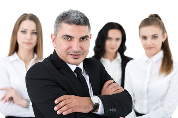 Smiling adult businessman standing in front of his colleagues