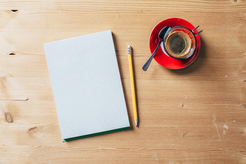 A recycled paper notebook checked with a black pencil with the eraser at the top and a cup of coffee with red saucer and spoon, are arranged on a brown wooden table. View from the top
