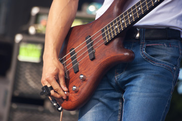 hand of bass guitarist in concert
