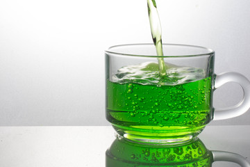 pouring green drink splash into glass on white background