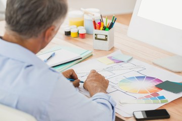 Creative businessman drawing plans using colour watch