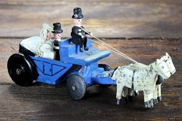 alte Hochzeitskutsche aus dem Erzgebirge auf Holzhintergrund