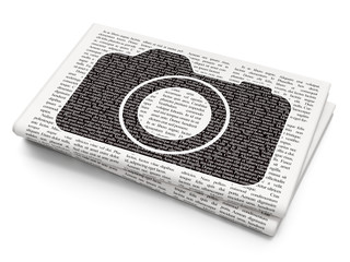 Travel concept: Photo Camera on Newspaper background