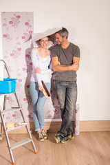 cheerful couple posing wallpaper on the walls of his house