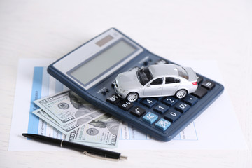 Toy car, money, documents and calculator on table. Car insurance concept