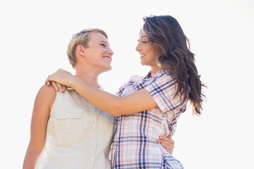 Smiling lesbian couple with arms around