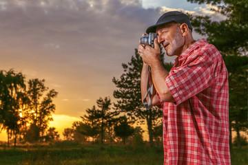 Senior photographer taking photos in nature.