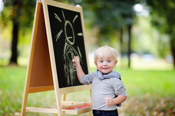 Toddler boy drawing standing by a blackboard