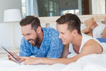 Happy homosexual couple looking at tablet computer