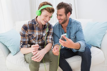 Homosexual couple men listening to music