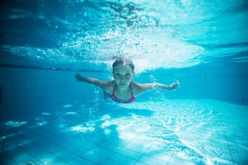 Child swims in pool underwater.