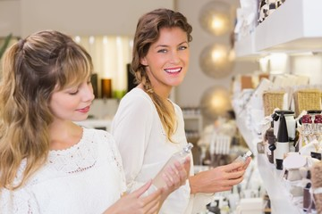 Beautiful friends holding perfume