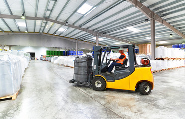 Workers with forklift in the depot - shipping // Logistikunternehmen - Gabelstaplerfahrer in einem industriellen Warenlager
