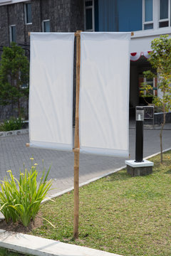 Blank white banner on a grass yard in front of an office, mock u